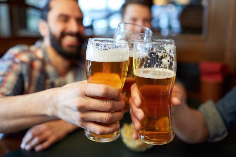 A group of men drinking beers at a bar | NYC premises liability lawyer