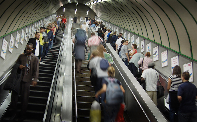 Crowded up and down escalators with stairs in the middle | Escalator Accident Attorney Reid B. Wissner