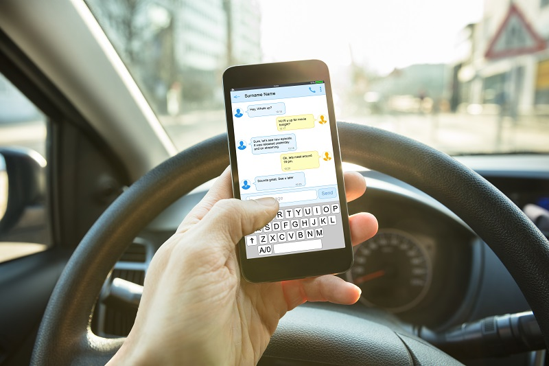 Person texting on phone while driving in car | Wissner Law | NYC